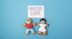 the inscription of paid sick leave with a gingerbread man in a medical mask. concept of state support during illness