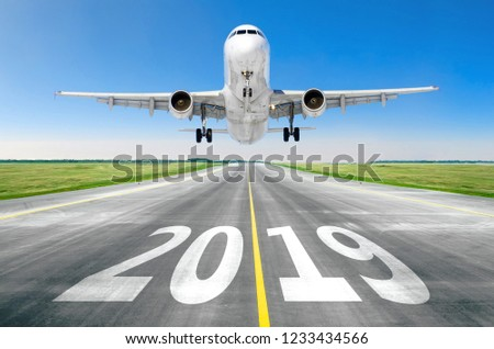 The inscription on the runway 2019 surface of the airport runway texture with take off airplane. Concept of travel in the new year, holidays
