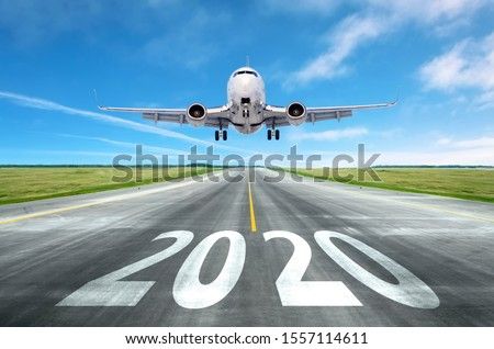 The inscription on the runway 2020 surface of the airport runway with take off aircraft. Concept of travel in the new year, holidays