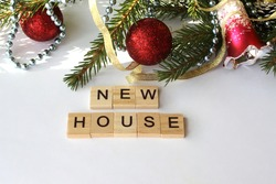 The inscription on wooden cubes is a new home, against the background of Christmas tree branches and balls. Close-up. There is a place for text. No people. The concept of buying a house, apartment, co