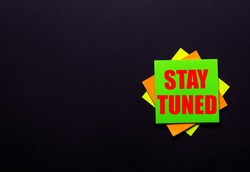 The inscription STAY TUNED on a bright sticker on a dark background. Copy space