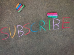 The inscription text on the grey board, SUBSCRIBE. Using color chalk pieces.