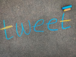 The inscription text on the grey board, TWEET. Using color chalk pieces. Post corona concept