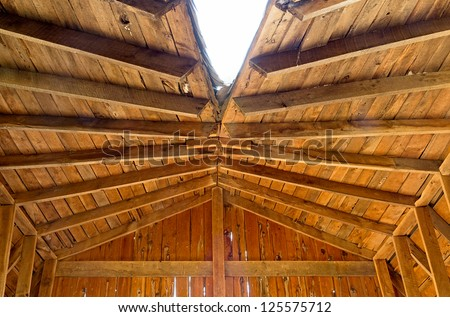 the inside view of a damaged wooden roof on an abandoned house