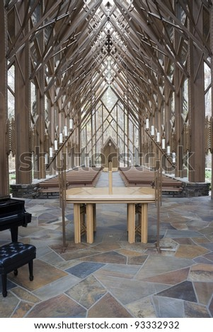 The insides of a wooden and glass church with alter