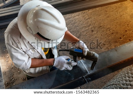 The inspectors are checking defect in welded of steel add joint with process Magnetic Particle Testing(MT) of Non-Destructive Testing(NDT) at industrial factory.