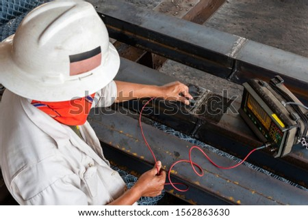 The inspectors are checking defect in welded of steel add joint with process Ultrasonic testing (UT) of Non-Destructive Testing(NDT), focus on hand that conducts the welding test.