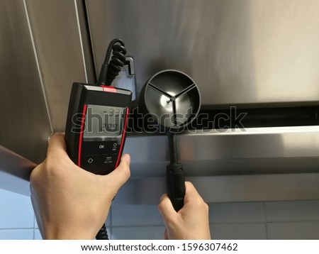 The inspectors are using anemometer to measure the air velocity of the hood in the kitchen.