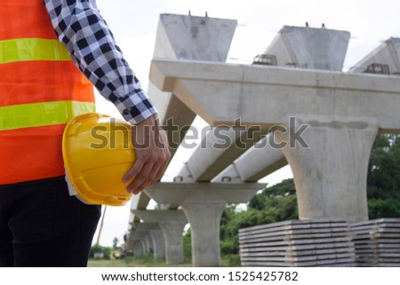 The inspectors or engineers are checking the work of the contractor team to build a bridge over the road.