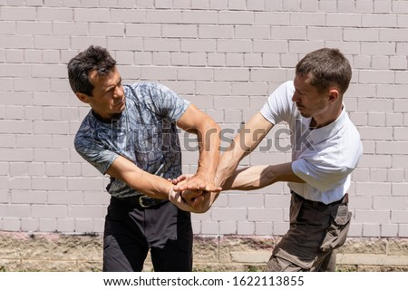 The interaction of the hands of the attacker and the defender. Martial arts instructors demonstrate self-defense techniques of Krav Maga