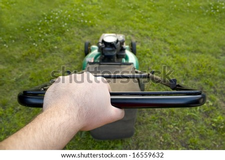 The interesting point of view from a man pushing a lawn mower. - stock photo