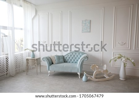 The interior is decorated in pastel blue tones with a vintage sofa.White walls with plaster stucco. Foto stock ©