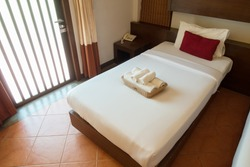 The interior of a hotel room and single bed.
