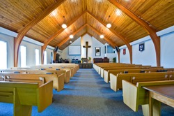 The interior of a simple church with a vaulted wooden ceiling and beams
