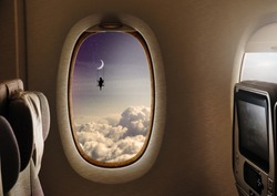The interior of an airplane flying in the sky and outside the town of the window shows the silhouette of a woman on a swing hanging from the moon. Concept of: dreams, flying, freedom.