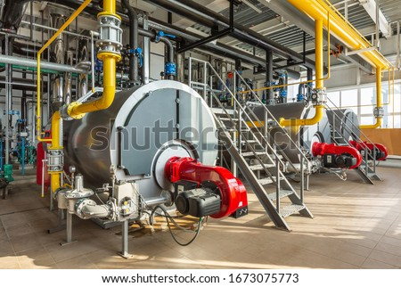 The interior of an industrial boiler room with three large boilers, many pipes, valves and sensors.