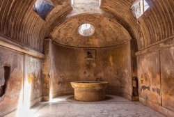 The interior of main public baths in ruins of Ancient Roman city Pompeii, Campania region, Italy. Sunny day. City destroyed by the eruption of Mount Vesuvius. Inside of Forum Baths. Big bowl for water