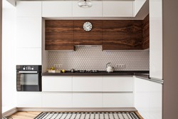 The interior of the beautiful trendy modern kitchen with white furniture, wooden inserts, combined wooden and mosaic floors and a large floor-to-ceiling window.