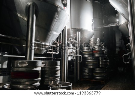 The interior of the brewery. Modern beer factory. Rows of steel stainless tanks for beer fermentation and maturation. Shop brewery. Geometry of plant. ストックフォト ©
