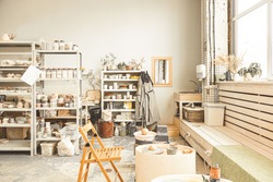 The interior of the creative workshop. shelves with finished products and materials and a pottery wheel for the manufacture of clay products