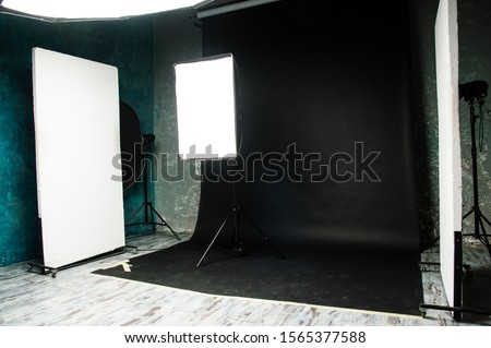 The interior of the photo studio. Preparing to work with photographic equipment. Black cyclorama, exposure to light on the octobox, softbox. Studio flags. Concept.