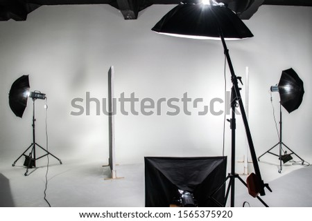 The interior of the photo studio. Preparing to work with photographic equipment. Cyclorama, background, exposure to light on the octobox, softbox. Studio flags.