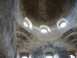 The interior of the ruins of an old abandoned brick church. Reinforcement of stone arches and vaults with metal rods. Arched windows with bright light.