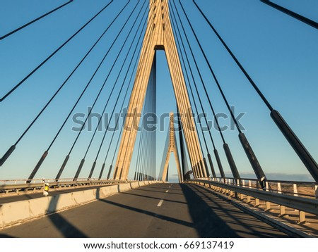 The International bridge, a suspension bridge between Spain and Portugal, looking towards Portugal and the Algarve with Ayamonte, Huelva Province, Andalucia behind crossing the Guadiana river. #669137419