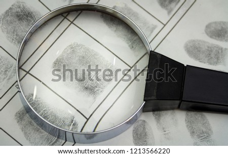 The investigation of the crime. A fingerprints and magnifying glass on a paper