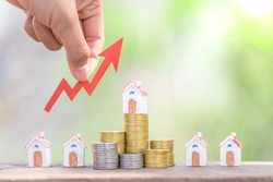 The investor's hand catches the red arrow.Business investment ideas.Concept of real estate investment.Business growth.House on a pile of coins.Stack of coins arranged in ascending order.