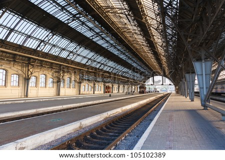 The iron arches and an empty platform of ancient Lviv Central Station early on a clear morning