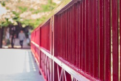 The iron railing fence is red. The picture is only partially clear.