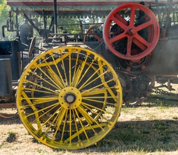 The iron spoked rear wheels and fly wheel of a vintage steam powered farm tractor, operating at Powerland Heritage Park at  the steam-up, in Salem Oregon