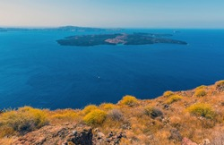 The islands of  Nea Kameni and Palea Kameni in Santorini's caldera viewed from Skaros Rock in summertime