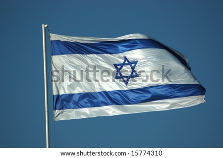 The Israeli flag flying against a bright blue sky.