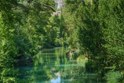The Júcar river as it passes through the city of Cuenca in Castilla-La Mancha (Spain) flows with green water surrounded by riverside trees on a sunny day.