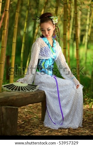 The Japanese with a fan, sitting on a bench in bamboo wood - stock photo