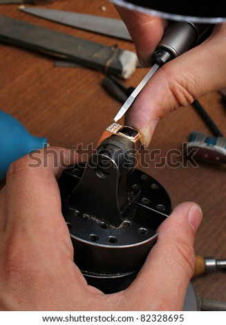 The jeweler is working at jeweler's workshop
