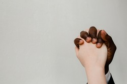 The joined hands of a black and European man on a light background. Unification, equality and the absence of oppression between members of different races.