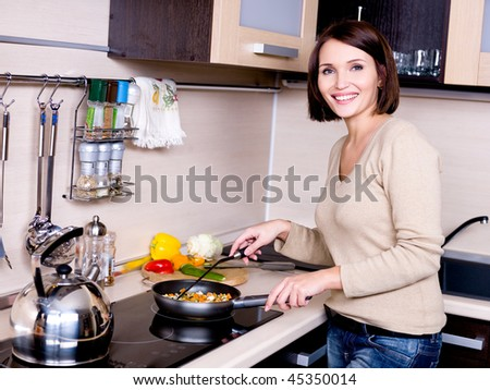 The joyful beautiful woman is on the kitchen prepares to eat