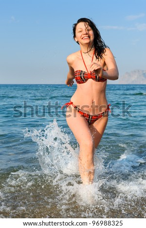 The joyful woman runs on sea water - stock photo