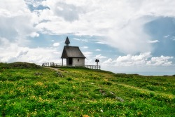 The Kampenwand. a popular hiking trail in the german alps. View of a beautiful old stone chapel on a meadow with flowers. Sunny summer day. Mountaineering. Aschau im Chiemgau, Bavaria.