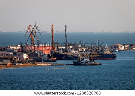 The Kerch Strait is clogged with vessels of different purpose, Black sea and Azov. The ship at anchor. A small port with fishing trawlers and a fish receiving base. #1238528908
