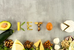 The keto word is from ketogenic food. Ketone diet foods on gray background with place for text.