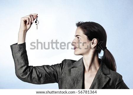 The Key to Success concept: Profile portrait of young business woman holding key between fingers.