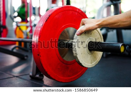The 5 kg white weight plate is being put on the barbell. To exercise in the class Of functional gyms.