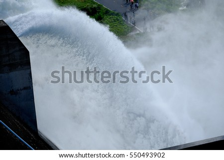 The Khun Dan Prakan Chon Dam, Water rushing through gates at a Largest cement dam in Nakhon Nayok,Thailand #550493902