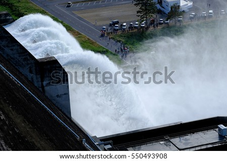 The Khun Dan Prakan Chon Dam, Water rushing through gates at a Largest cement dam in Nakhon Nayok,Thailand #550493908