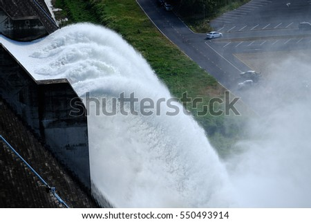 The Khun Dan Prakan Chon Dam, Water rushing through gates at a Largest cement dam in Nakhon Nayok,Thailand #550493914