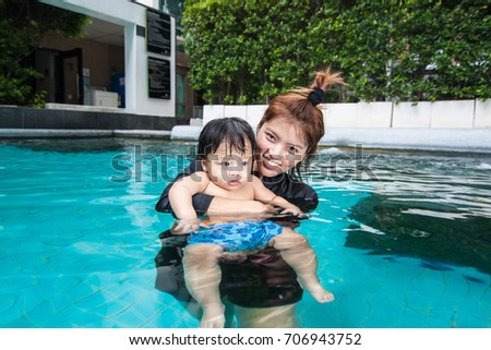 The kid and mom play together in the pool, in the condominium